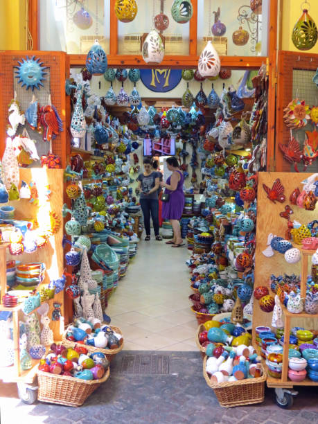 Tourist buying souvenirs in colorful pottery shop in Chania, Crete