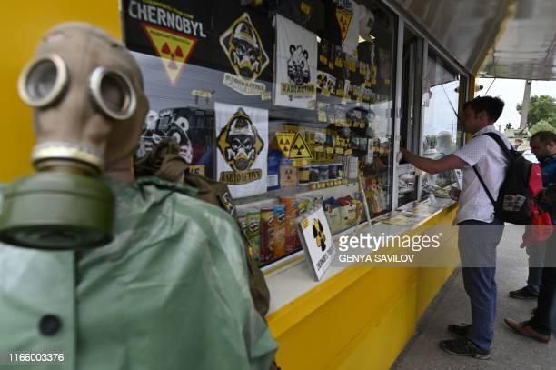 Tourist buys souvenirs in the stall on the checkpoint of a 30-kilometer Chernobyl exclusion zone around the plant, Ukraine, on August 1, 2019. - The...