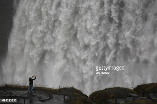 A tourist captures the scene at a waterfall known as Dettifoss on June 2 2017 in Vatnajokull National Park Iceland Iceland's tourism industry...