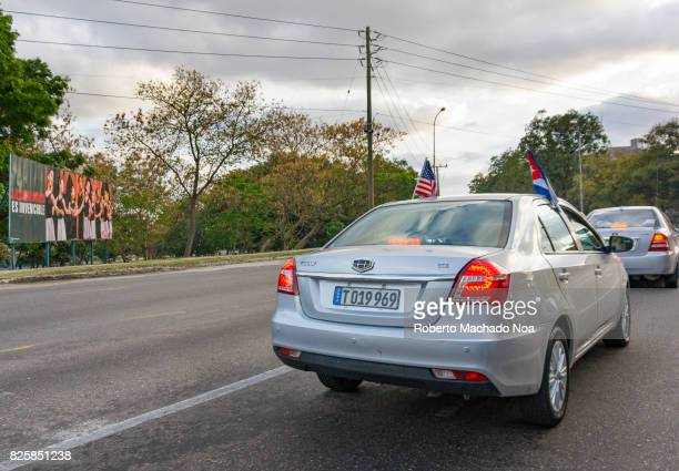 Tourist car with the Cuban and United States flag waving together Backside of two silver cars passing down a road lined with trees