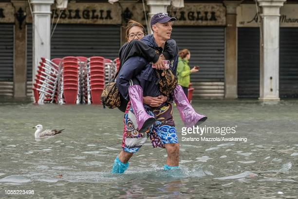 A tourist carries his girlfriend through the water on October 29 2018 in Venice Italy Due to the exceptional level of the acqua alta or High Tide...