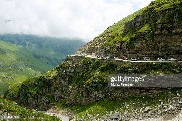 Tourist cars queue up on a mountain road