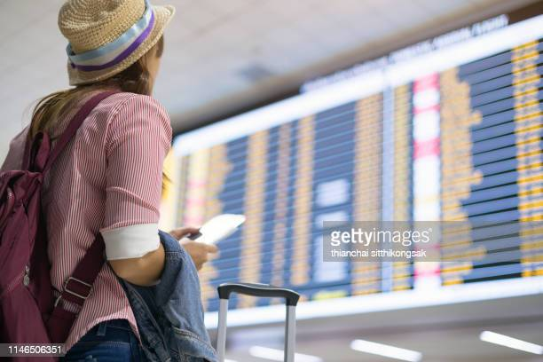 tourist checking time board at airport - arrival stock pictures, royalty-free photos & images