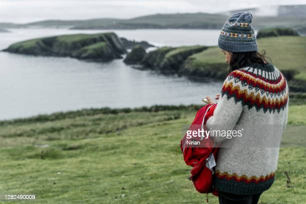 tourist checks the phone in the shetland islands - warm clothing stock pictures, royalty-free photos & images