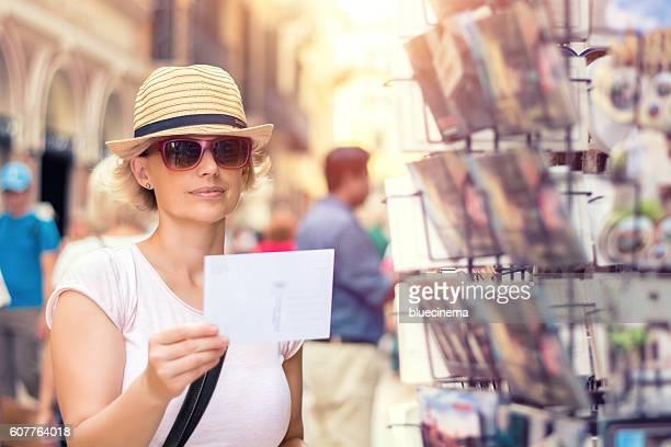 Tourist choosing postcard on the city