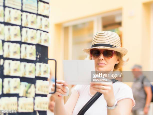 tourist choosing postcard on the city - gift shop stock photos and pictures