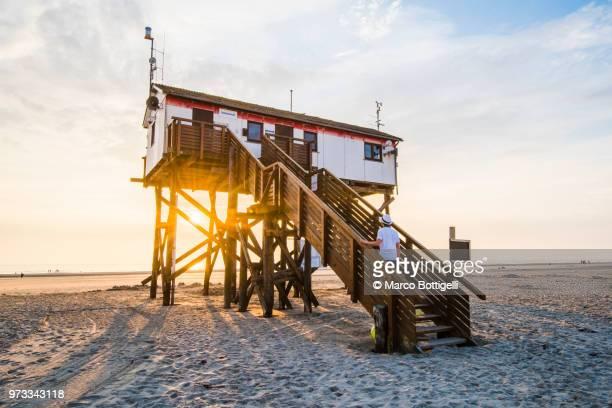 Tourist climbing a stilt house on the wadden sea, Germany.