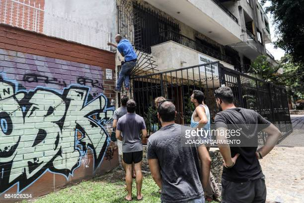 Tourist climbs a fence on September 19, 2017 next to the house where druglord Pablo Escobar spent his last days and was killed as he tried to escape,...