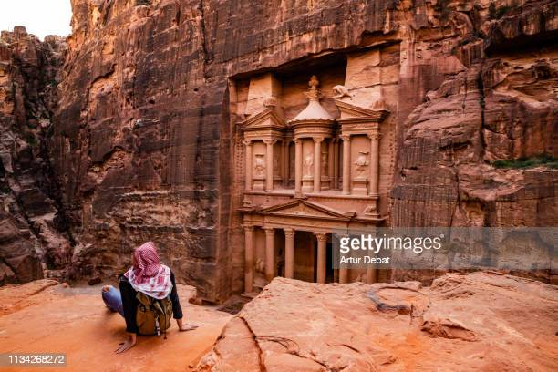 tourist contemplating the al-khazneh treasury tomb in the city of petra from viewpoint. - jordan middle east stock pictures, royalty-free photos & images
