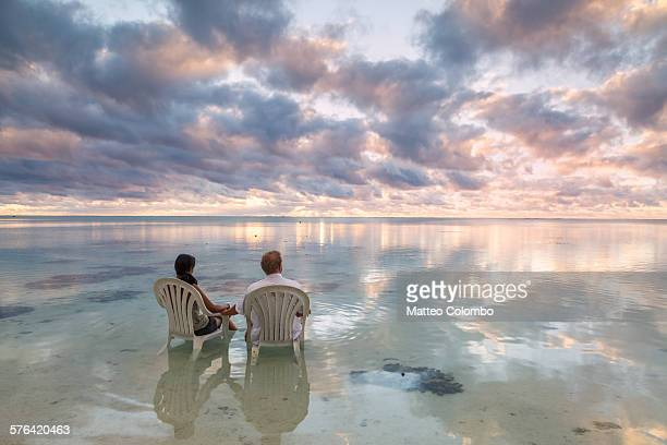 Tourist couple admiring sunset on the sea Aitutaki