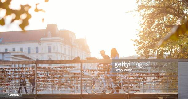 tourist couple cycling over bridge - slovenia stock pictures, royalty-free photos & images