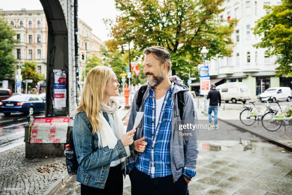 Tourist Couple Deciding Where To Go Using Leaflet : Stock Photo