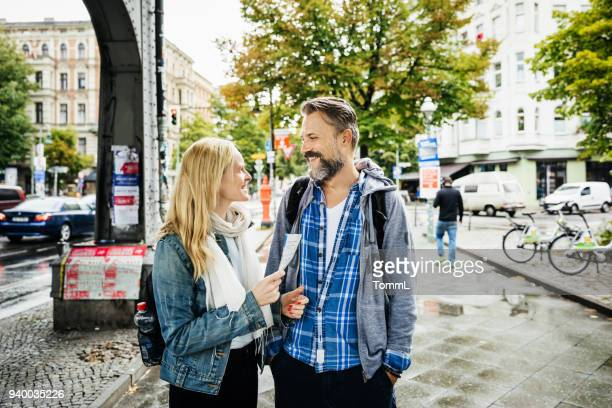 tourist couple deciding where to go using leaflet - flyer leaflet stock photos and pictures