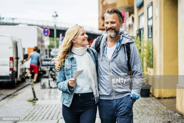 tourist couple embrace while out exploring the city - mature couple stock pictures, royalty-free photos & images