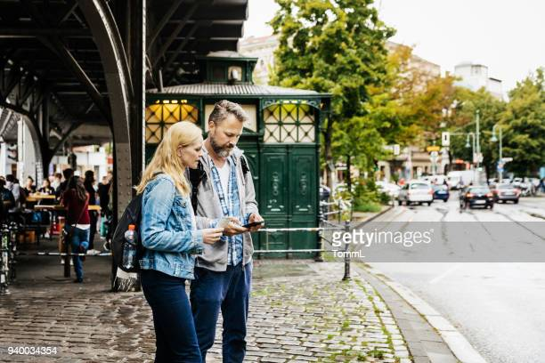 tourist couple finding their bearings in new city - berlin stock pictures, royalty-free photos & images