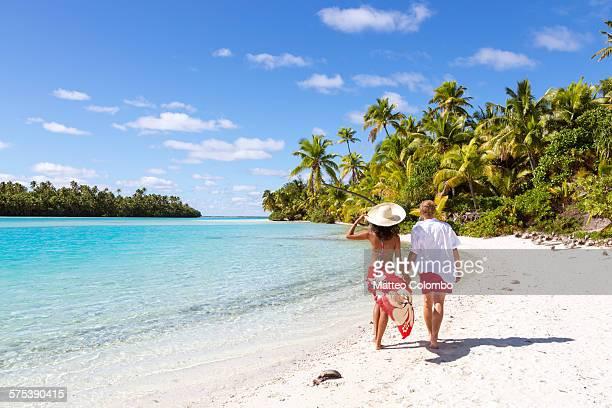 Tourist couple hand in hand walking on beach