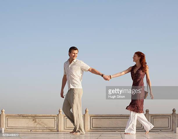 tourist couple holding hands - hugh sitton stock pictures, royalty-free photos & images