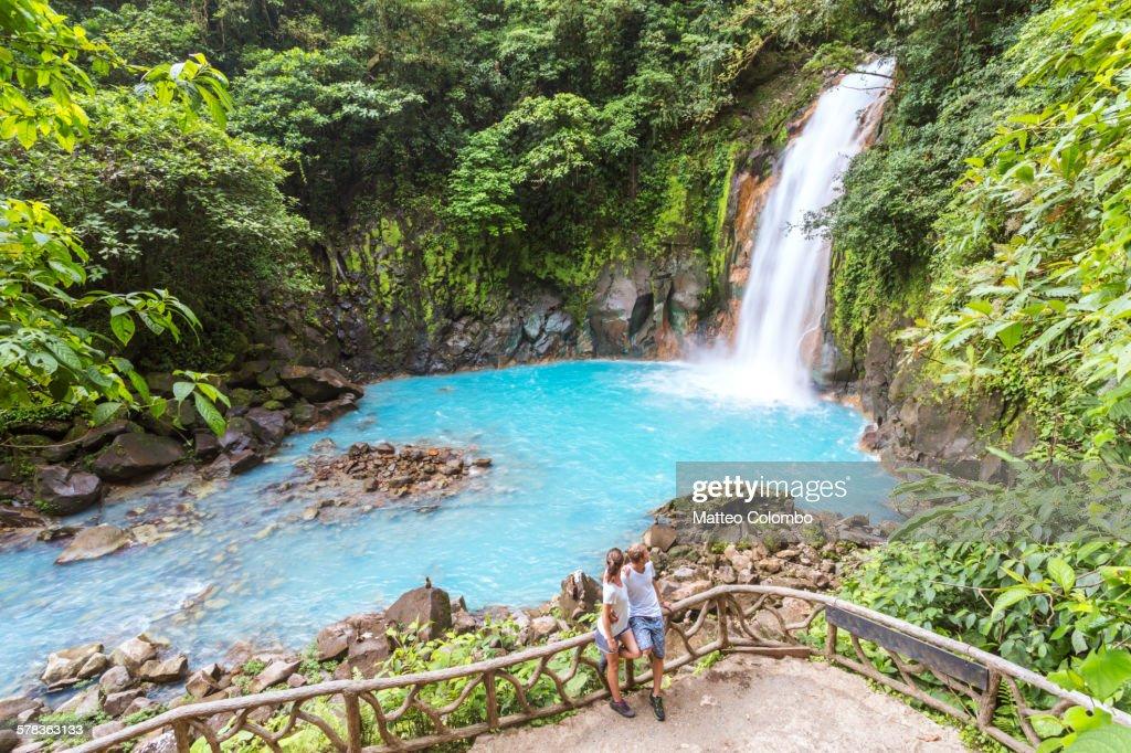 Tourist couple looking at Rio Celeste waterfall : Stock Photo