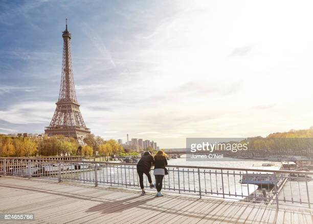 tourist couple looking at the eiffel tower, paris, france - paris stockfoto's en -beelden