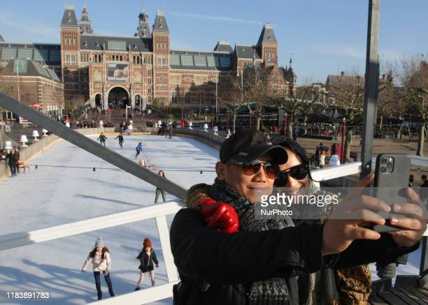 A tourist couple make a self on the bridge over the ice rink in front of the Rijksmuseum in the Museum Square during sunny winter day on November 22...