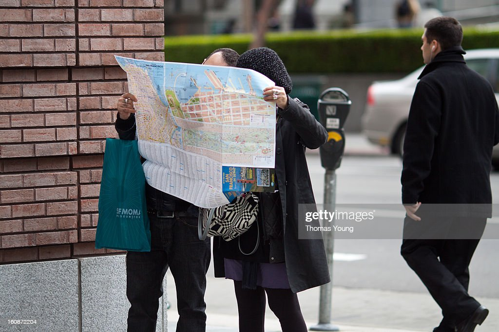 CONTENT] A tourist couple reading a map outside of SFMOMA, San Francisco. Lost. Directions. Map.