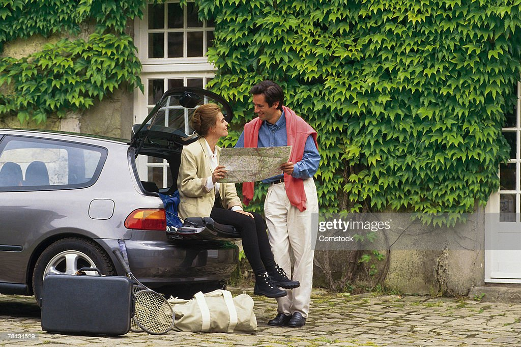 Tourist couple reading map by car : Stockfoto