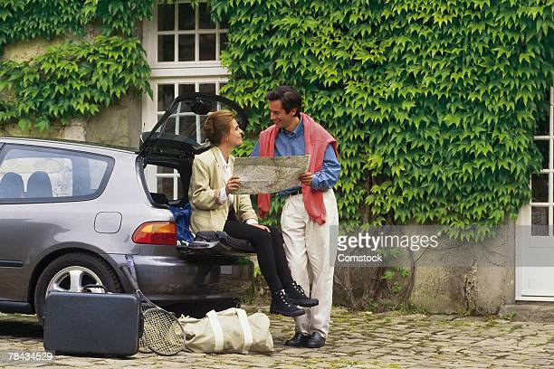 Tourist couple reading map by car