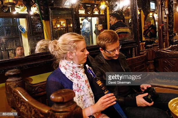 A tourist couple relax with a sheesha also known as a waterpipe or nargilla at the elFishawi coffee shop made famous by the Egyptian Nobel prize...