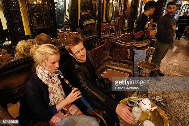 A tourist couple relax with a sheesha also known as a waterpipe or nargilla fresh lemonade and mint tea at the elFishawi coffee shop made famous by...