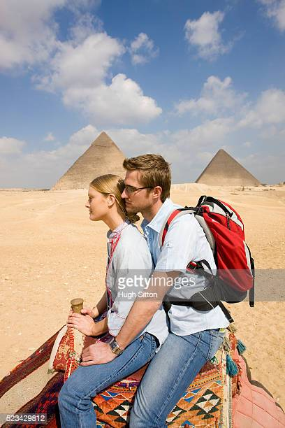 tourist couple riding camel by pyramids of giza - hugh sitton stock pictures, royalty-free photos & images