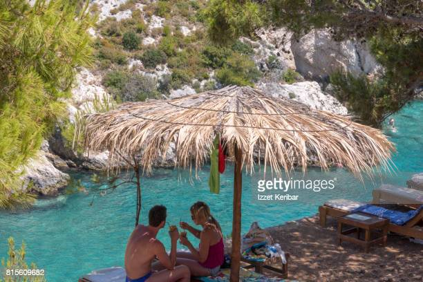A tourist couple sipping a drink under a straw umbrella at Limnionas beach, Zakynthos  Ionian Islands, Greece