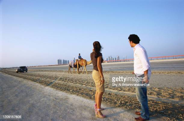 tourist  couple standing on a roadside, looking away, dubai, uae. - incidental people stock pictures, royalty-free photos & images