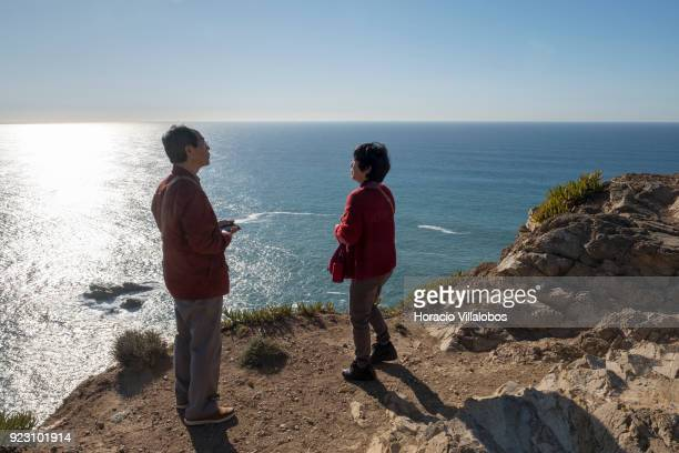 A tourist couple stands by the edge of the cliff on a sunny winter afternoon in Cabo da Roca on February 22 2018 in Sintra Portugal Cabo da Roca is a...