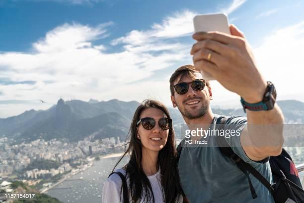 pares do turista que tomam um selfie em rio de janeiro usando um telefone - turismo urbano - fotografias e filmes do acervo