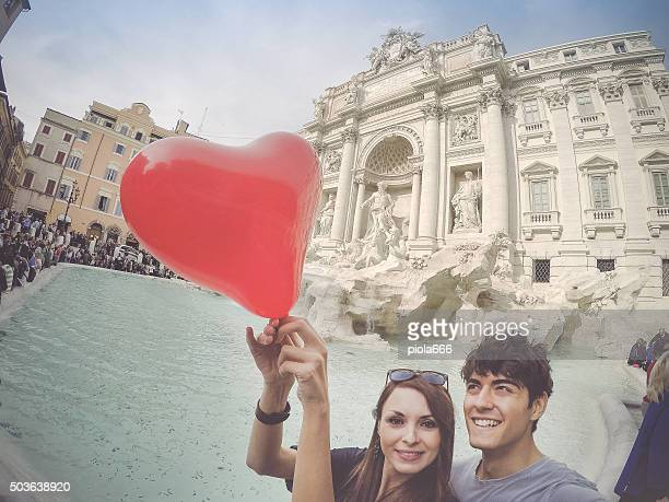 Tourist couple taking a selfie with heart at Trevi fountain