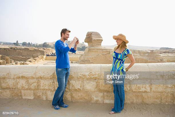 tourist couple taking pictures by the great sphinx at giza - hugh sitton stock pictures, royalty-free photos & images