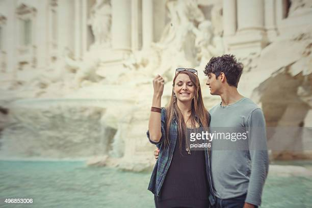 Tourist couple throwing a coin in the Trevi fountain