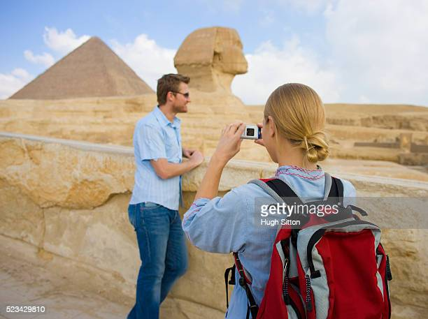 tourist couple using camera while sightseeing at the great sphinx at giza - hugh sitton stock pictures, royalty-free photos & images
