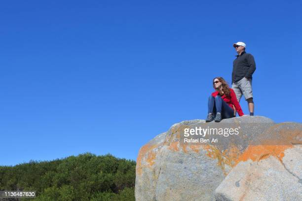 Tourist couple visit at the  Bay of Fires in Tasmania Australia