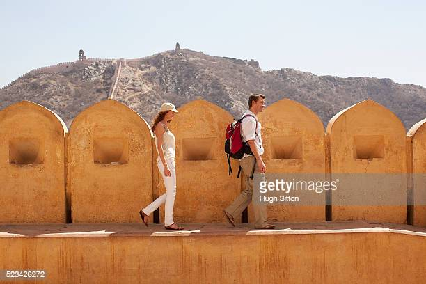 tourist couple walking along wall of jaipur fort - hugh sitton stock pictures, royalty-free photos & images