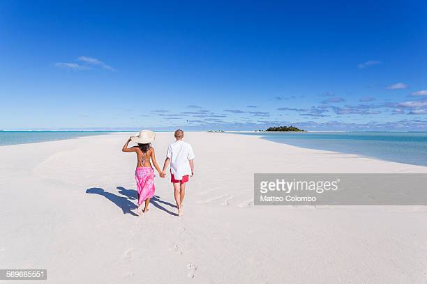 Tourist couple walking on deserted tropical island