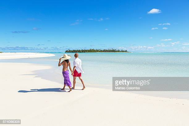 Tourist couple walking on sandy beach, Aitutaki