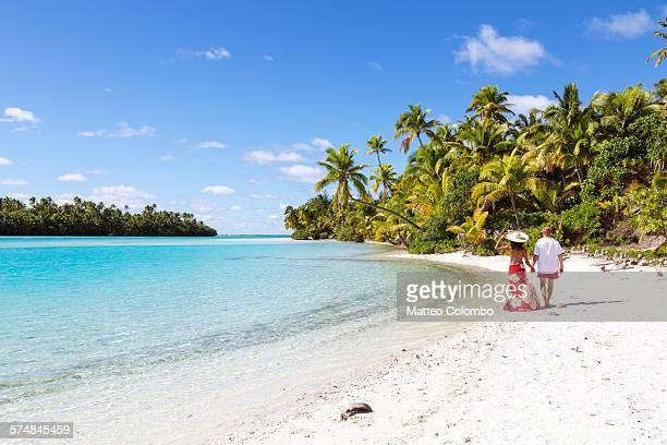 Tourist couple walking on tropical beach, Aitutaki