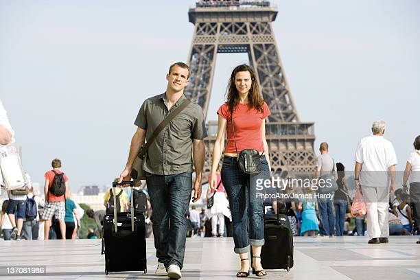 Tourist couple walking with their luggage near Eiffel Tower, Paris, France