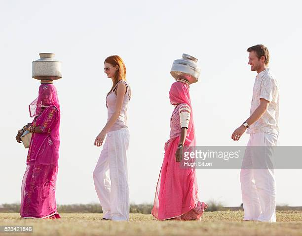 tourist couple walking with two indian women wearing saris and carrying waterjugs - hugh sitton stock pictures, royalty-free photos & images