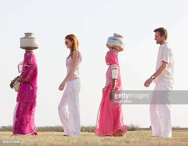 tourist couple walking with two indian women wearing saris and carrying waterjugs - hugh sitton fotografías e imágenes de stock
