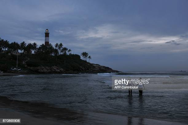 A tourist couple walks hand in hand in the Arabian sea during sunset at Kovalam Beach in Thiruvananthapuram on November 6 2017 / AFP PHOTO /...
