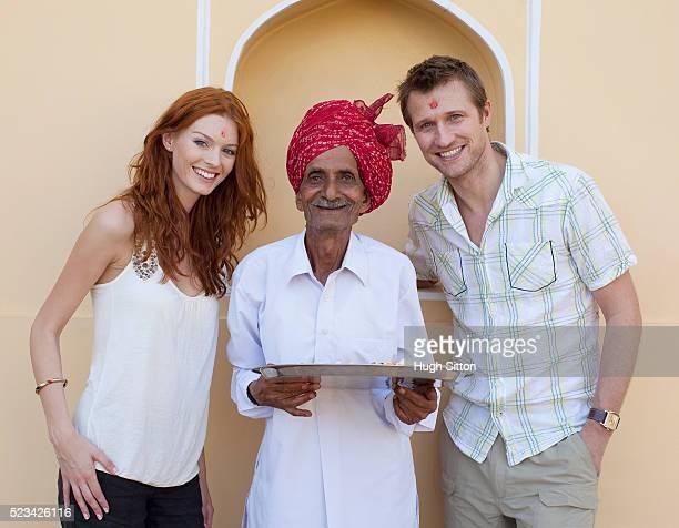 tourist couple with a rajasthani man - hugh sitton stock-fotos und bilder