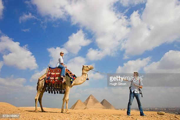 tourist couple with camel at the pyramids of giza - hugh sitton stock pictures, royalty-free photos & images
