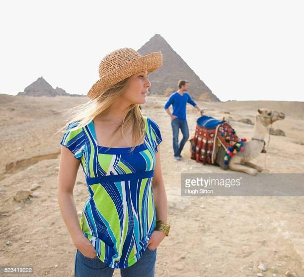 tourist couple with camel at the pyramids of giza - hugh sitton stockfoto's en -beelden